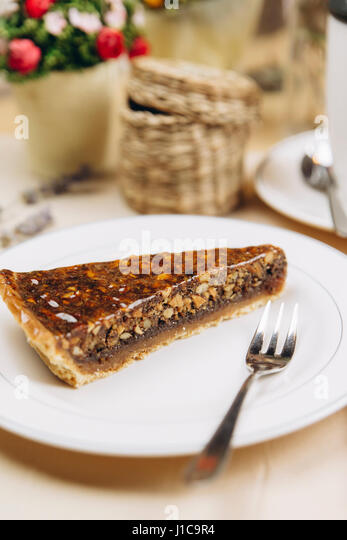 Slice of caramel tart on plate with fork - Stock Image