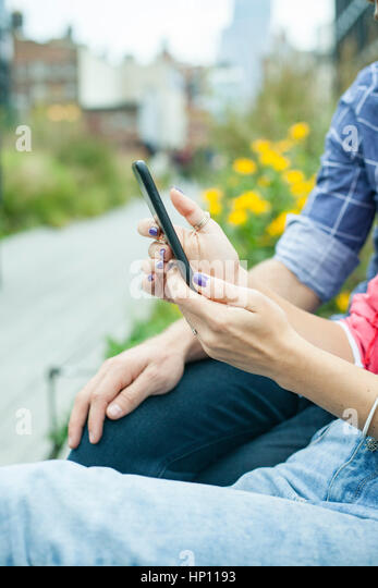 Couple using smartphone outdoors, cropped - Stock Image