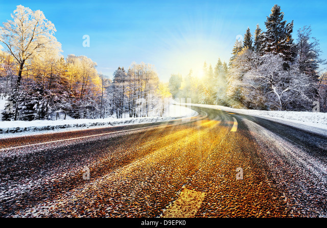 Winter road in winter with sunlight reflecting on asphalt - Stock Image