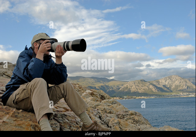 Man photographer taking a photograph of a landscape with telephoto lens, South Western Cape, South Africa - Stock-Bilder