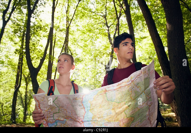 young man and woman got lost during hiking excursion and look for destination on map. Horizontal shape, waist up - Stock Image