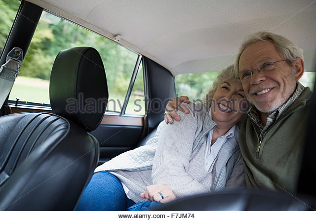 Senior couple hugging and smiling back seat car - Stock Image