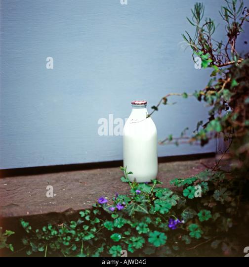 A glass milk bottle on a doorstep in Llanthony, Ewyas Valley, Wales, UK  KATHY DEWITT - Stock Image