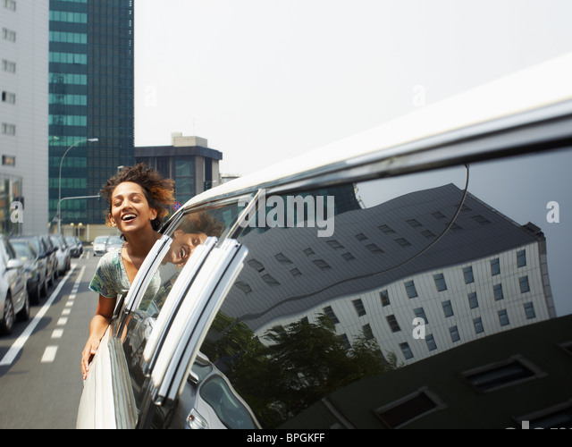woman with head out of limousine window - Stock Image