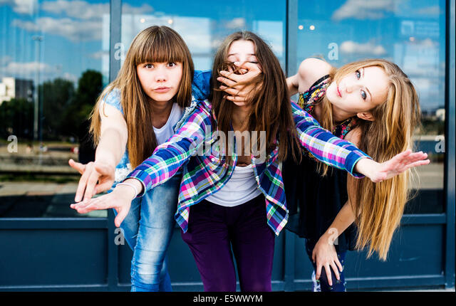 Three young women in a row leaning forward and covering mouth - Stock Image