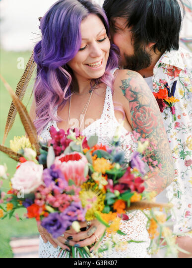 Sweden, Groom kissing bride at hippie wedding - Stock Image