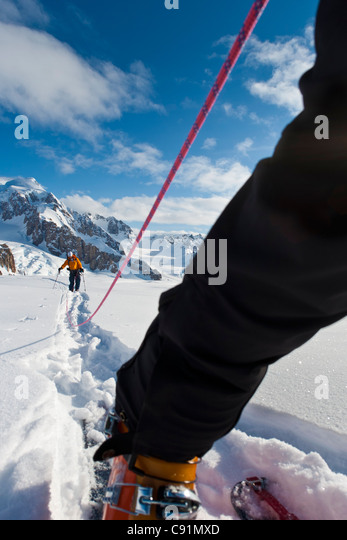 Low angle view of roped skiers leaving the camp on the Triumvirate Glacier  to climb Mount Torbert, Tordrillo Mountains, - Stock Image