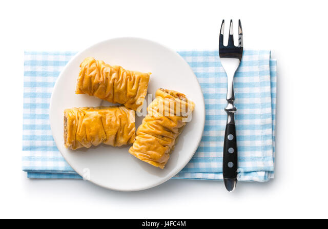 Sweet dessert baklava on napkin with fork. Isolated on white background. Top view. - Stock Image