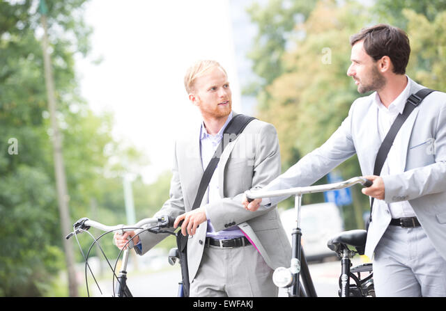 Businessmen looking at each other while holding bicycles outdoors - Stock-Bilder