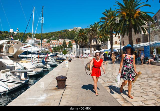 Tourists on a luxury holiday at Hvar Town Harbor, Hvar Island, Dalmatian Coast, Croatia, Europe - Stock Image