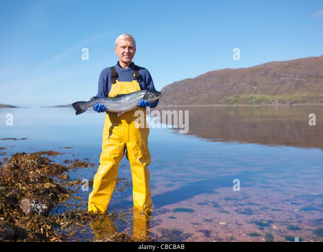 Fisherman holding salmon by lake - Stock Image