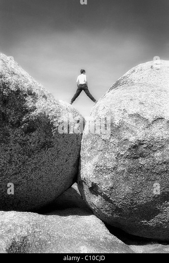 Woman straddles two large boulders while looking out onto the horizon. - Stock Image