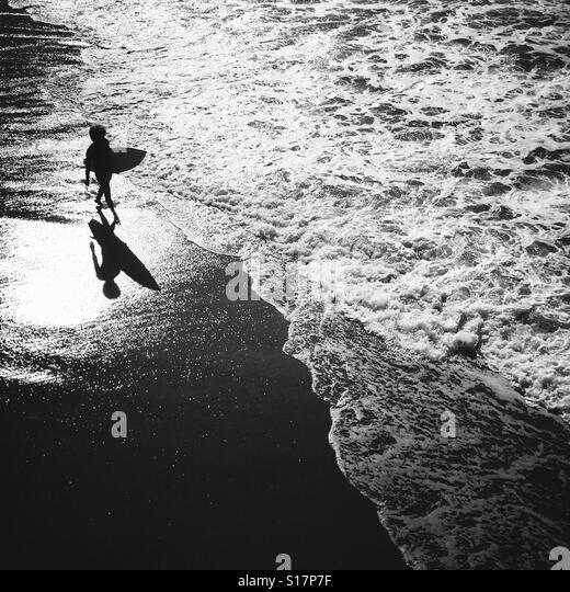 A surfer waking on the beach. Manhattan Beach, California USA. - Stock Image