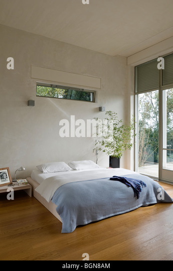 Bedroom with wooden floor in contemporary house - Stock-Bilder