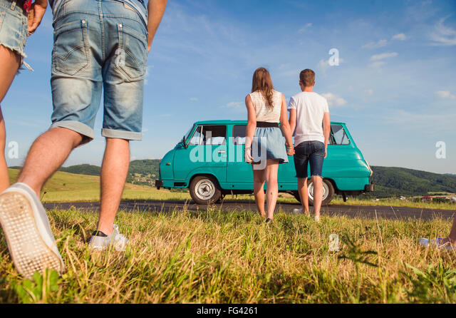 Couples in love, nature, blue sky, campervan, back view - Stock-Bilder