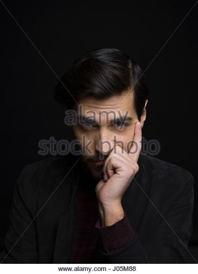 Portrait serious handsome brunette man with head in hand against black background - Stock Image