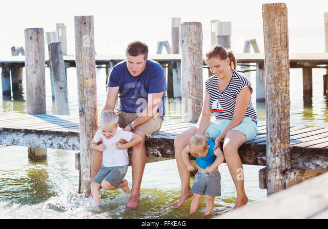 Family sitting on the pier, above water, sunny summer - Stock-Bilder