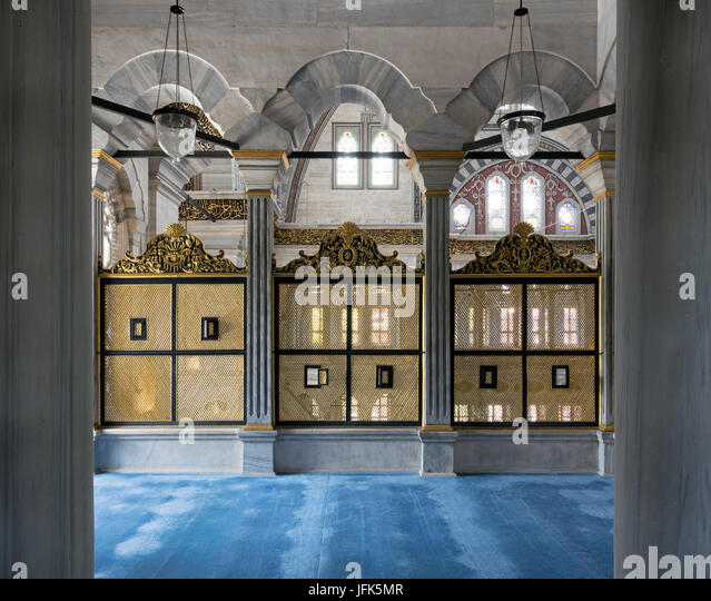 Three gold painted decorated Interleaved wooden windows (Mashrabiya) framed by three marble arches, marble wall - Stock Image