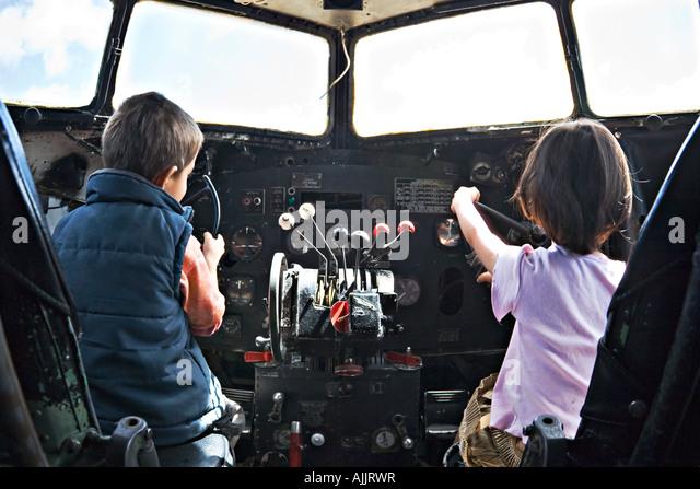 Boy and girl play in cockpit of old DC 3 Douglas Dakota - Stock Image