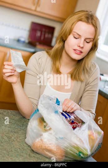 Woman checking shopping prices - Stock Image