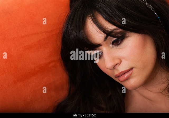 A young woman in makeup on a sofa. - Stock Image