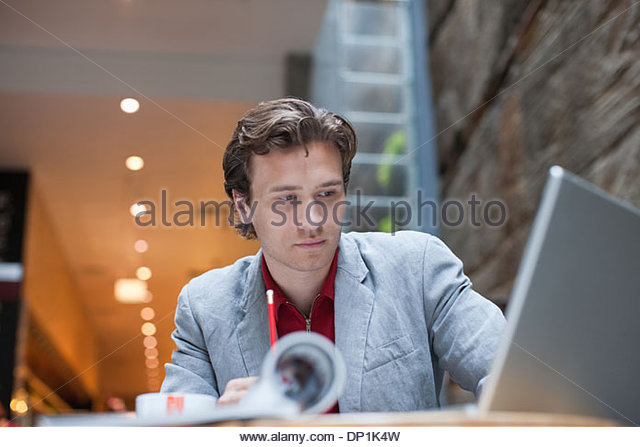 Businessman with laptop at table looking pensive - Stock-Bilder