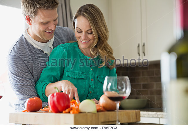 Husband embracing wife as she prepares food in kitchen - Stock Image