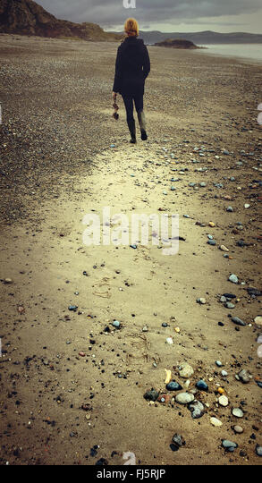 woman walking in distance on the beach holding  drift wood - Stock Image