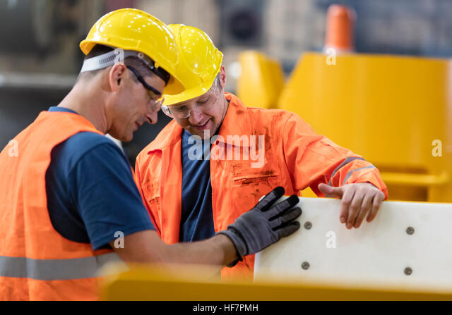 Workers examining part in factory - Stock Image