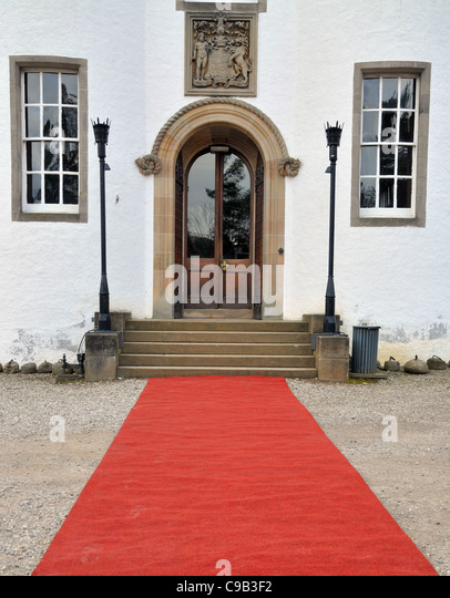 A red carpet laid out at the front entrance of Blair castle, Pitlochry, Perth. - Stock Image