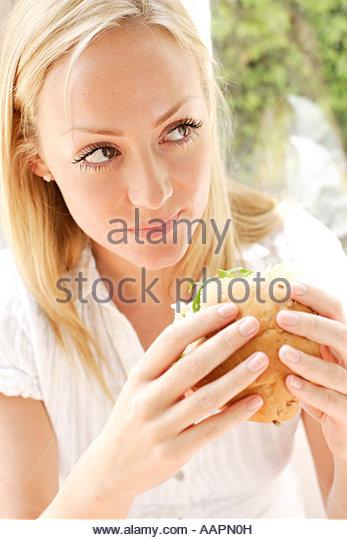 Blonde girl eating healthy sandwich - Stock-Bilder