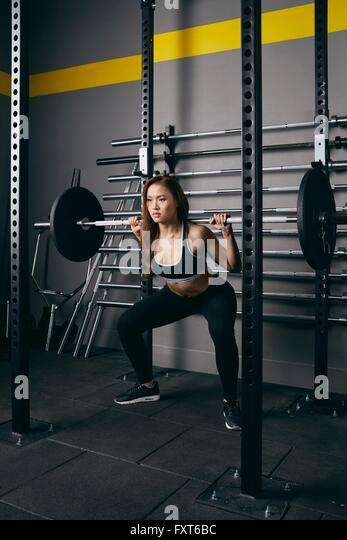 Young woman weightlifting with barbell on shoulders at gym - Stock Image