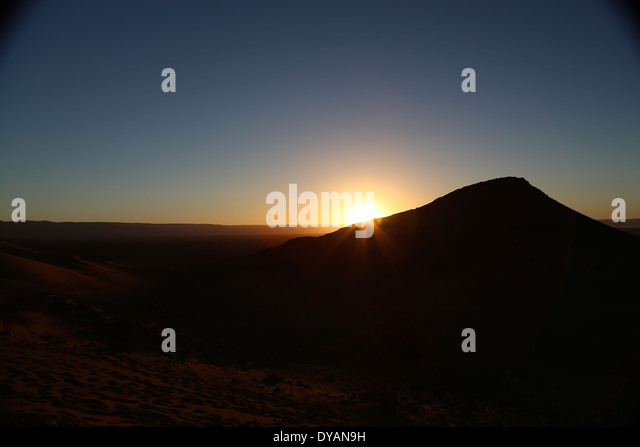 Sunrise over baron desert landscape in Morocco beyond the Atlas mountain ranges, with rays of sunlight overlapping - Stock Image
