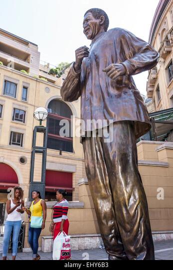 South Africa African Johannesburg Sandton Nelson Mandela Square statue Black woman friends - Stock Image