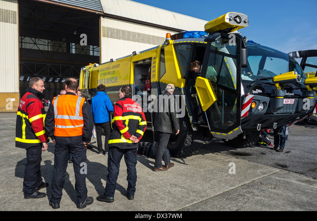 Firefighters and airport crash tender Rosenbauer Panther CA-5 6×6 at the Ostend aerodrome, Belgium - Stock Image