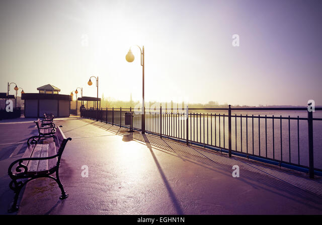 Retro vintage filtered nostalgic picture of promenade against sun. - Stock Image