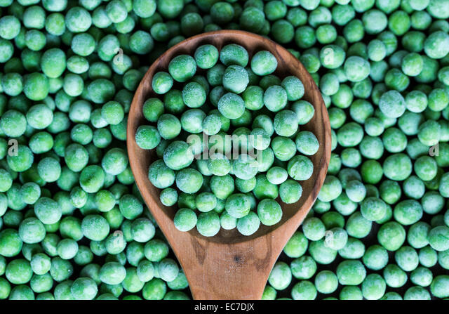 Wooden spoon and frozen peas - Stock Image