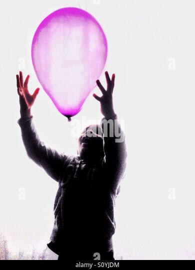 Boy catching a Pink balloon. - Stock-Bilder