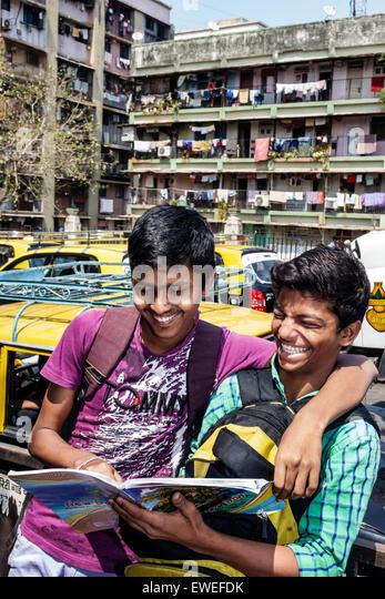 Mumbai India Indian Asian Tardeo Jehangir Boman Behram Road teen boy friends student reading studying book smiling - Stock Image