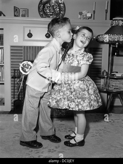 j1950s LITTLE BOY IN SUIT AND TIE TRYING TO KISS LITTLE GIRL IN PARTY DRESS - Stock-Bilder