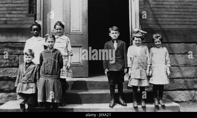 Full length portrait of two groups of children; three Caucasian children, two girls and one boy, on the right side; - Stock Image