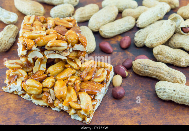 Honey bar with peanuts almonds and hazelnuts surrounded by bunch of roasted and raw peanuts placed on a wooden board - Stock Image
