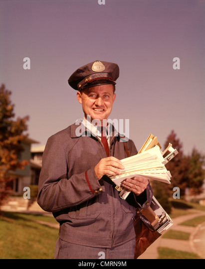 1960 1960s SMILING MAILMAN HOLDING LETTERS MAIL MAILBAG UNITED STATES POSTAL SERVICE USPS MAILMEN DELIVERY - Stock Image