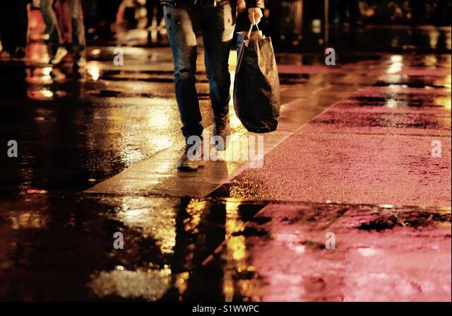 Shopper crossing the wet pavement at night - Stock Image