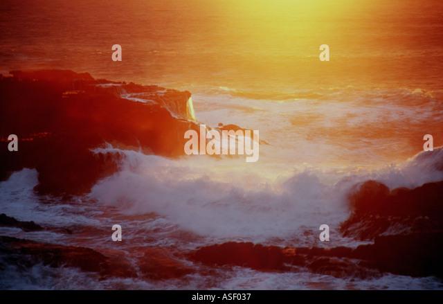 Waves breaking on rocky shoreline at sunset Piha New Zealand - Stock Image