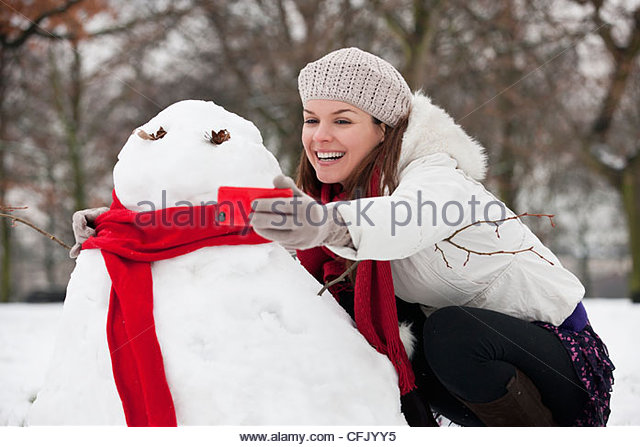 A young woman taking a photograph of a snowman - Stock Image