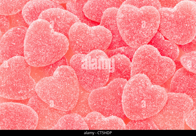 A background of sugar coated red heart shaped jelly candy - studio shot - Stock Image