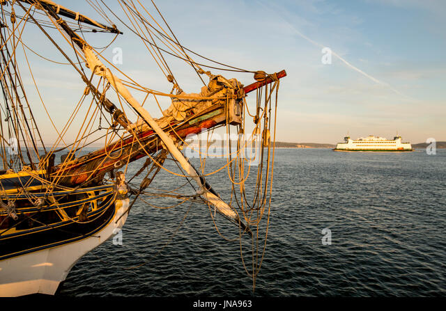 Port Townsend ferry passes by replica of Lady Washington sailing boat. - Stock Image