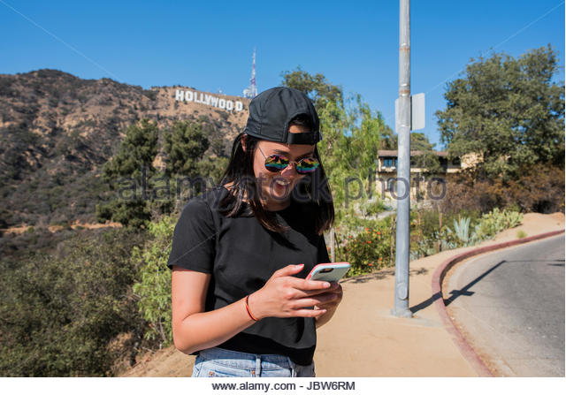 Young woman reviewing smartphone near Hollywood sign, Los Angeles, California, USA - Stock-Bilder