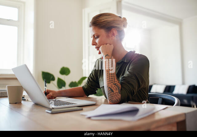 Shot of young woman working at home office. Beautiful female sitting at table with laptop and documents. - Stock Image